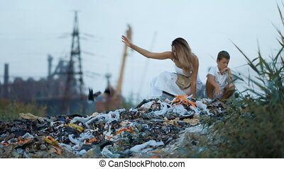 Mom and son. Garbage dump. Industrial factory on a...