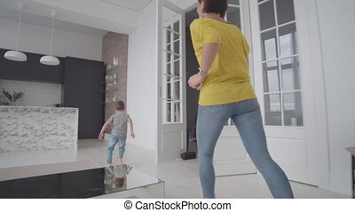 mom and son have fun playing catch-up at home in a white...