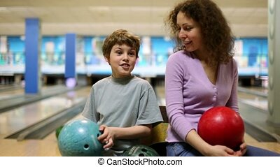 Mom and son hold bowling balls in hands and talk in bright club