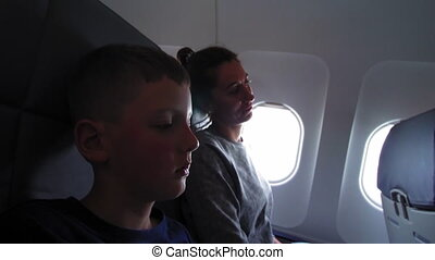 Mom and son in airplane cabin, child ready for new...