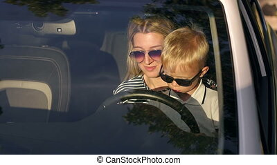 Mom and son in sunglasses sitting together at the wheel of the car.
