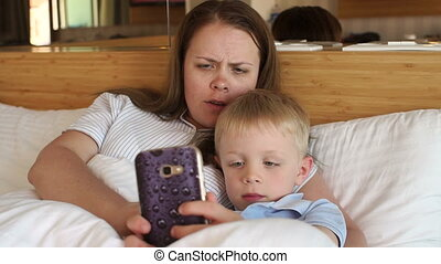Mom and son lie on the bed under the blanket and play games on the phone.