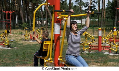 Mom and Son on Street Exercise Machines go in for Sports