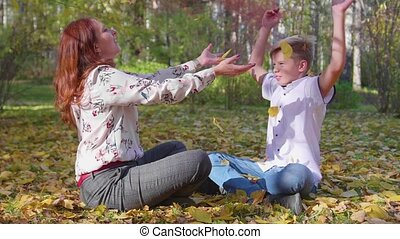 Mom and son play in the autumn Park. They throw yellow...