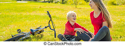 Mom and son rest on the lawn after riding a bike BANNER, LONG FORMAT
