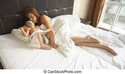 mom and son sleep in the morning in bed at