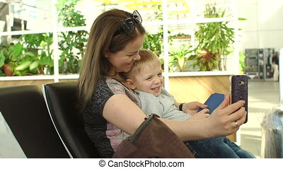 Mom and son take a selfie on the phone at the airport in the waiting room.