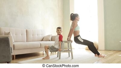Mom and son training together does exercise for hand triceps at home, side view. Sporty fit family doing fitness aerobic exercises for hands in living room. Home workout training and wellness concept.
