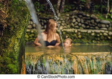 Mom and son travelers in Belulang Hot Springs in Bali, ...