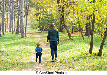 Mom and son walking in the park at sunset