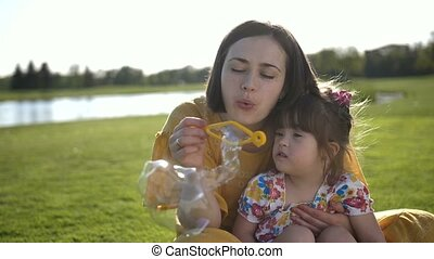 Mom and special daughter blowing bubbles in park - Young...