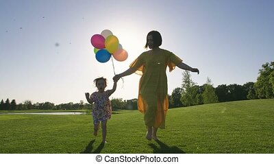 Mom and special needs girl running with baloons - Mother and...