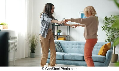 Mom and teen girl dancing holding hands enjoying music in modern apartment