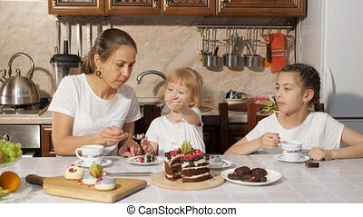 Mom and two daughters are having a tea with homemade chocolate cake in the kitchen, family birthday at home.