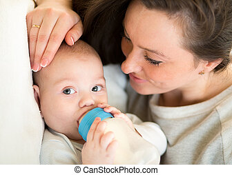 mom at home feeding baby boy with a milk bottle