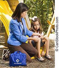 Mom bandaging scrape. - Hispanic girl sitting on playground...