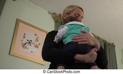 Mom Bouncing and Comforting Baby - A mom comforting and...