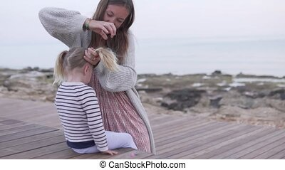 Mom braids the hair of a little girl on the beach by the sea.