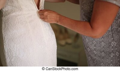 Mom button up the bride's dress. Dressing up wedding dress.