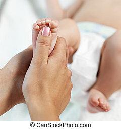 Mom checks reflex child on foot