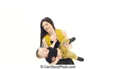 Mom circulates his child in his arms. White background. Slow motion