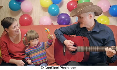 Mom, dad and a small child play the guitar sing, dance and have fun