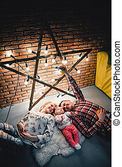 mom, dad and baby lie on a woolen carpet and smile