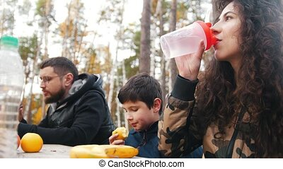 mom, dad and child sitting near to each other outdoors in the woods at the table and enjoy meal. Front view. Focus on drinking woman