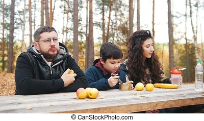 mom, dad and child sitting near to each other outdoors in the woods at the table and enjoy meal.