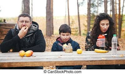 mom, dad and child sitting near to each other outdoors in the woods at the table and enjoy meal. Front view