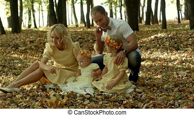 Mom, dad and children having fun in a clearing in the park among the fallen maple leafs