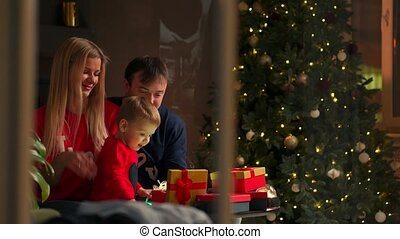 Mom dad and son at Christmas open gifts at home sitting on the couch in the Christmas interior. Warm and cozy home atmosphere