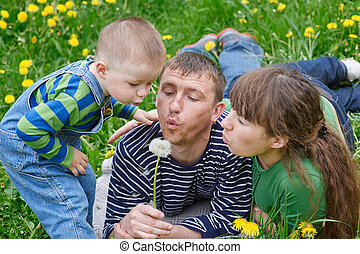 mom dad and son together blowing on a dandelion in a meadow