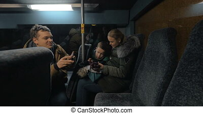 Mom, dad and son traveling bus in the evening and using cellphones