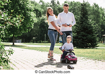 mom, dad, and son walking down a path in a city Park.
