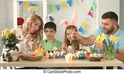 Mom, dad, son and daughter sitting and drawing on Easter eggs together