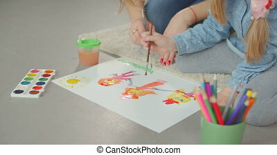 Mom developing creativity of child through painting -...