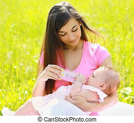 Mom feeding baby bottle outdoors