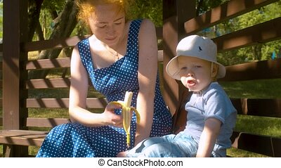 Mom feeding baby boy in the park
