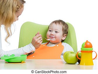 Mom feeding her kid with a spoon. Mother giving food to her little child. Baby food and nutrition.
