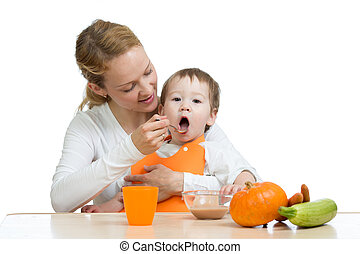 Mom feeding her kid with a spoon. Mother giving food to her little child. Healthy baby food and nutrition.