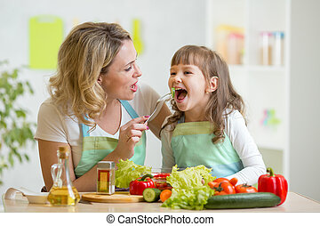 mom feeding kid daughter vegetables in kitchen