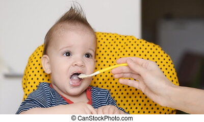 Mom feeds a one year old toddler at home porridge - Mom...