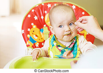 Mom feeds funny baby from a spoon . child eats in a highchair
