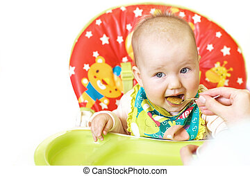 Mom feeds funny baby from a spoon on a white background. child eats in a highchair