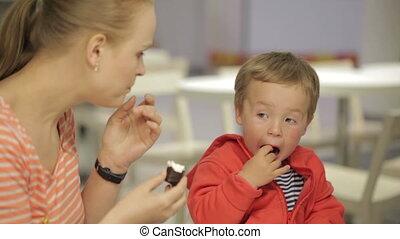 Mom feeds her son in restaurant