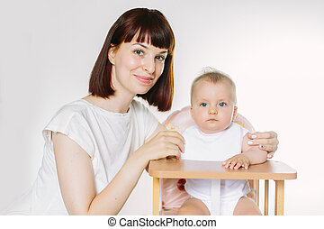 Mom feeds the baby in a baby chair with a spoon.