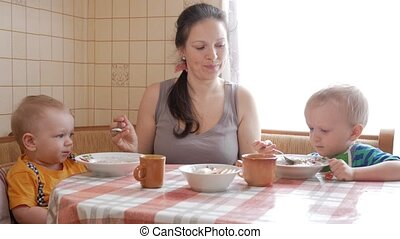 Mom feeds two sons of the house porridge at the table. One boy himself eats with a spoon. The second child helps a woman.