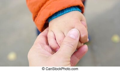 mom gently pats the hand of a small child closeup