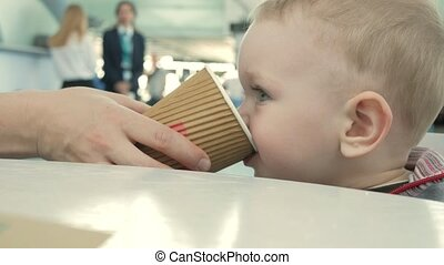 Mom gives her a cup of tea for the airport. The boy enjoys a...